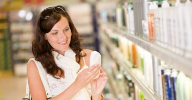 Shopping cosmetics - smiling woman holding shampoo in supermarket