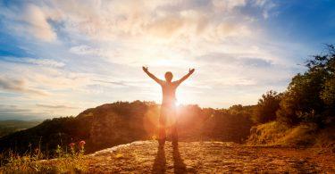 夕日の前で両手を掲げる男性