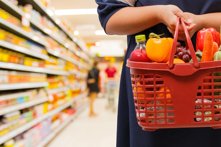 woman holding shopping basket in supermarket