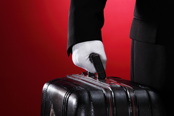 Hotel porter carrying suitcase