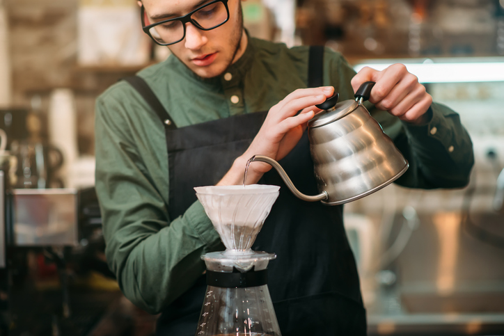 Waiter pours hot boiled water in a coffee pot