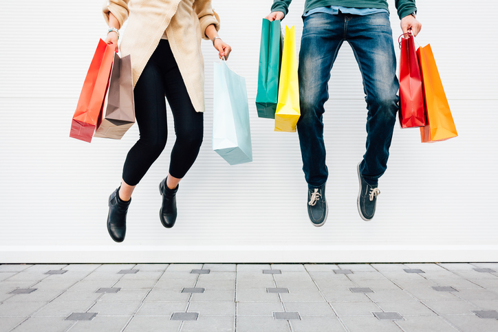 Woman and man jumping with shopping bags