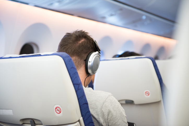Man use earphone via sit in cabin on plane.