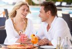 Couple eating pizza and drinking tropical drinks outside