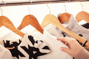 female hand selects new fashion clothes on wood hangers on rack,