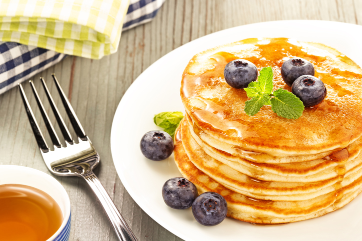 plate of stacked pancakes with fresh blueberries