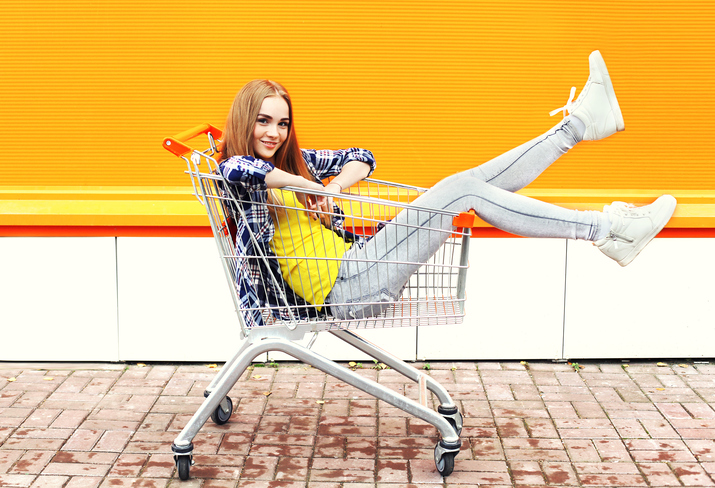 Fashion cool girl having fun sitting in shopping trolley cart