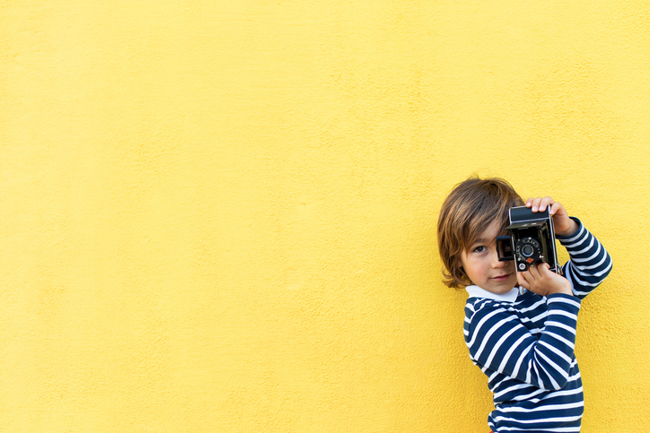 little boy taking a picture with a vintage camera