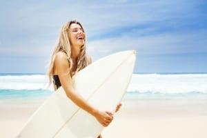 young woman in black bikini with her surfboard
