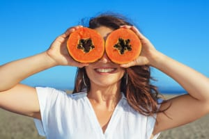 Adult woman hold in hands ripe fruit - orange papaya