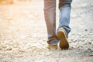 Lonely man wearing jeans and leather boots walking