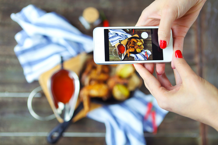 Woman taking photo of hot meat dishes on wooden background