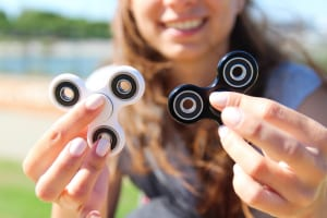 Smiling Women hold a white and black spinner