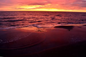 Sea waves during a colorful sunset over a romantic beach