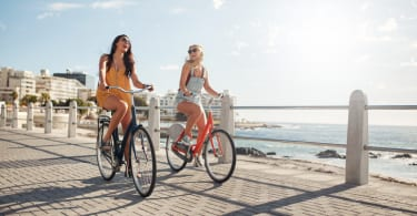 Female friends riding their bicycles on the promenade