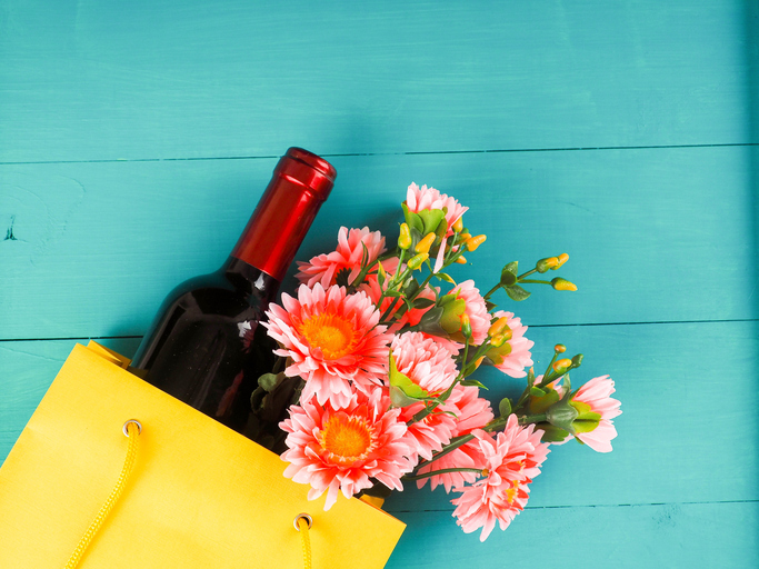 bottle of wine and flowers in the package on wooden background, space for text