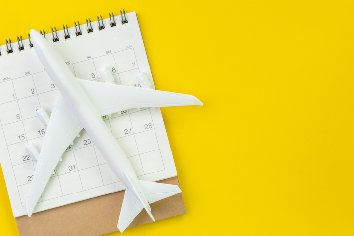 Travel schedule or planning, tourist, vacation, flat lay or top view of miniature airplane and calendar on vivid yellow background table with blank copy space