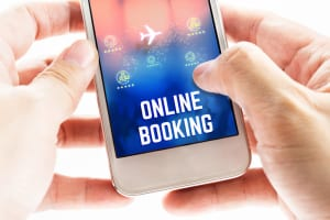 Close up Two hand holding mobile phone with online booking word and icons, Online Digital Marketing concept