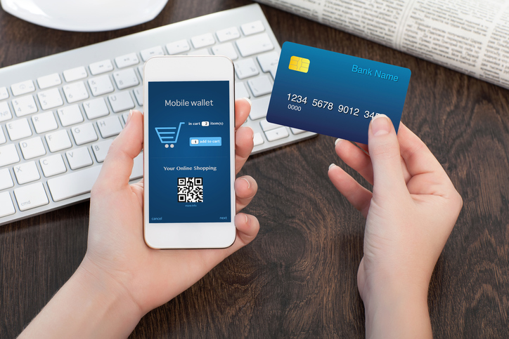 female hands holding credit card and phone in the office and making a purchase onlain