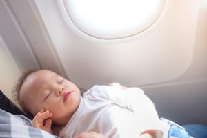 Cute little Asian 18 months / 1 year old toddler baby boy child sleeping on Airplane with copy space