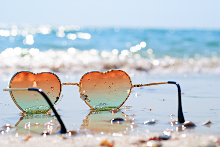 Photo of heart-shaped glasses on the beach