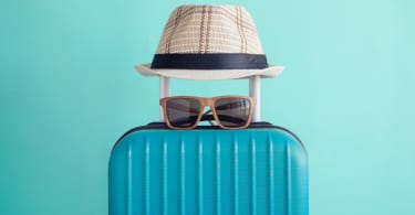 Luggage with woven beach hat and sunglasses on green background minimalistic vacation concept